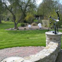 Sitzmauer und Sockel aus Sandstein, Pflasterfläche aus Betonstein, Rollrasen und Kiesbeet mit Bepflanzung