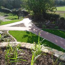 Ein Hochbeet aus Sandsteinmauern fängt den Höhenunterschiede von der Terrasse zum Rasen ab.
