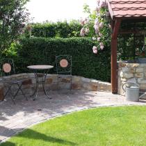 Gartensitzecke mit Mauer und Brunnen aus Sandstein