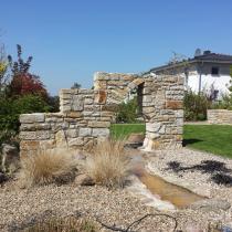 Erweiterung eines Steinbeetes: Bachlauf und Sprudelstein unter Sandsteinmauer