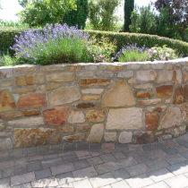 Sandsteinhochbeet als Höhenabfang und Terrasse aus Betonstein