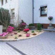 Eingangstreppe aus Granitplatten und -Steinen, Hochbeet und Mülleinhausung aus Granitstelen, Betonsteinpflasterung, Beet mit Granitsteineinfassung und Miskantusbett