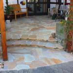 Terrasseneingang aus Quarzitplatten mit Hochbeeten aus antiken Sandsteintrögen