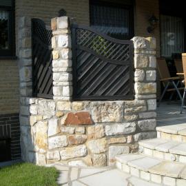 Wir haben Sichschutzzaunelemente in eine Sandsteinmauer integriert. Diese Lösung ist ein Unikat und wurde im Zuge des gesamten Terrassenkonzepts erstellt.