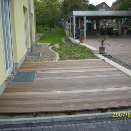 Eine Holzdeckterrasse, vor dem Traufstreifen aus Kies.
