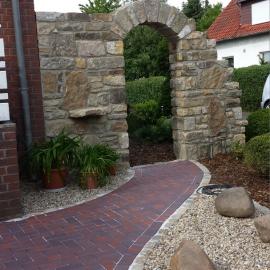 Torbogen aus Sandstein, Steinbeet mit Granitfindlingen