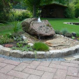 Steinbeet mit einem Sprudelstein-Findling als Mittelpunkt