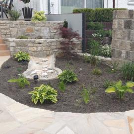 Zaunelemente in Sansteinmauer eingearbeitet neben Bachlauf und Hochbeeten aus Sandstein