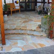 Eingangsgestaltung mit Quarzitplatten und Sandsteinwassertrögen als Beetkästen
