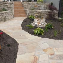 Gartenkonzept mit Sandsteinweg, Terrasse mit Hochbeeten und Bachlauf aus Sandstein