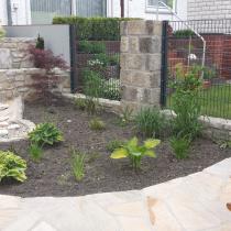 Zaunelemente in Sandsteinpfeiler eingemauert, Gartenkonzept mit Sansteinweg, Terrasse mit Hochbeeten und Bachlauf aus Sandstein