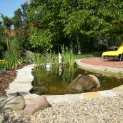 Garten- und Teichgestaltung: Teich mit Quarzitplatteneinfassung, Betonsteinpflaster, sowie einem Kies- und einem Rindenmulchbeet