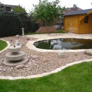 Teichgestaltung mit Natursteineinfassung, Sitzfläche mit Quarzitplatten, Kiesbeet mit Sprudelstein