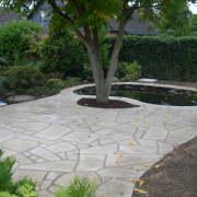Teich- und Baumeinfassung aus Sandsteinplatten gehen in eine Terrassenfläche über