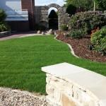 Rollrasen, Rasenkante und Banksitzfläche aus Quarzit, Natursteinmauer und Einfassung, Mulchbeet mit Findlingen